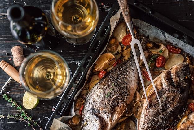 Madre cocina la cena para toda la familia, hornea pescado dorado
