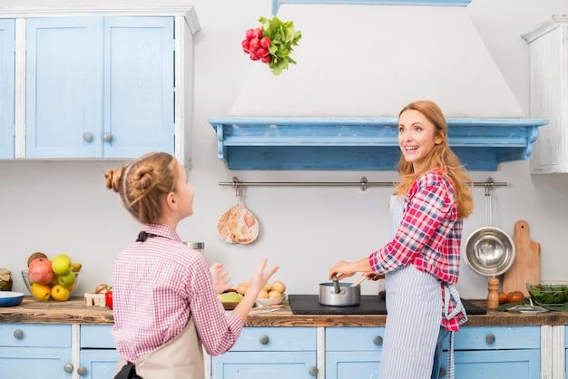 Madre cocinando comida mirando a su hija lanzando rábanos en el aire en la cocina