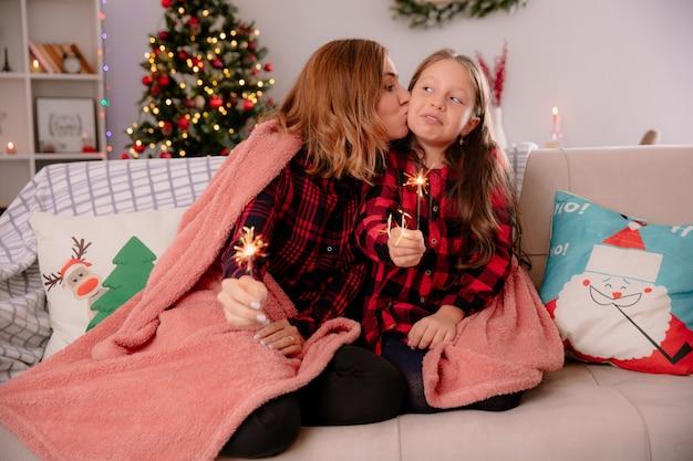 Madre complacida besa a su hija y sostiene bengalas cubiertas con una manta sentada en el sofá y disfrutando de la navidad en casa