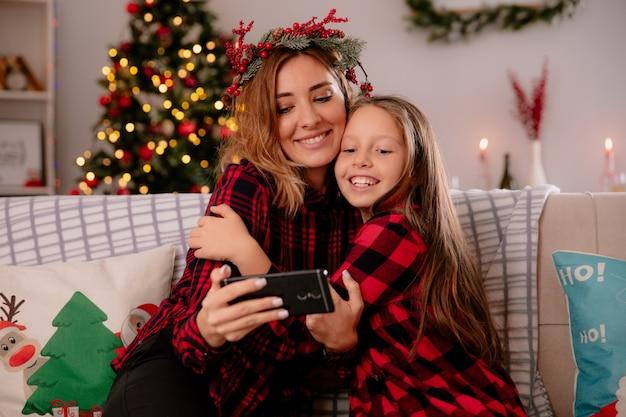 Madre complacida con corona de acebo e hija viendo algo en el teléfono sentado en el sofá y disfrutando de la navidad en casa