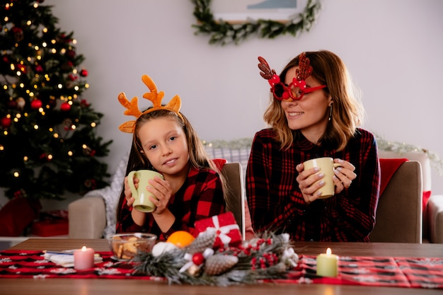 Madre complacida en gafas de reno mirando a su hija sosteniendo la taza sentada a la mesa disfrutando de la época navideña en casa