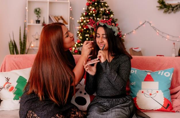 Madre complacida haciendo maquillaje a su hija con corona de acebo sentada en el sofá disfrutando de la navidad en casa