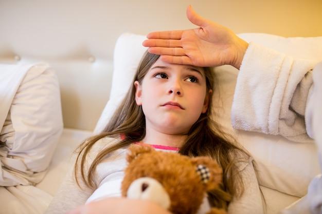 Madre de comprobar la fiebre de su hija en el dormitorio