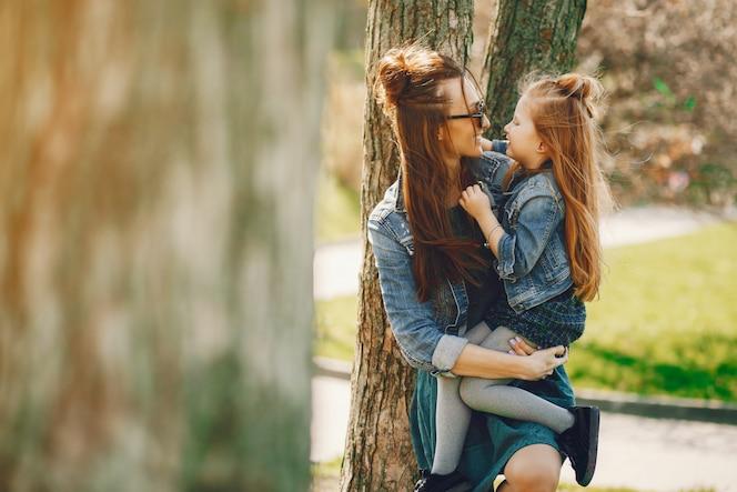 Madre con estilo con el pelo largo y una chaqueta de jeans jugando con su pequeña hija linda