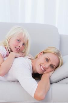 Madre con su hija acostada en el sofá en la sala de estar