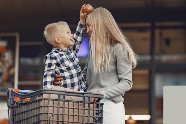 La madre conduce un tranvía. familia en un parking cerca de un supermercado.