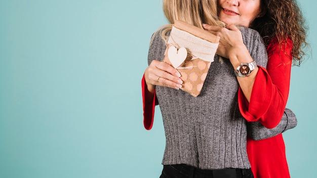 Madre de cosecha que abraza a hija para el regalo