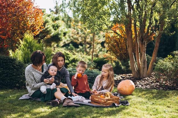 Madre con cuatro hijos haciendo un picnic en el patio trasero