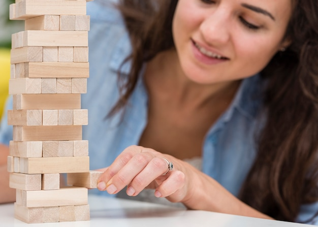 Madre cuidando mientras consigue una pieza de un juego de torre de madera
