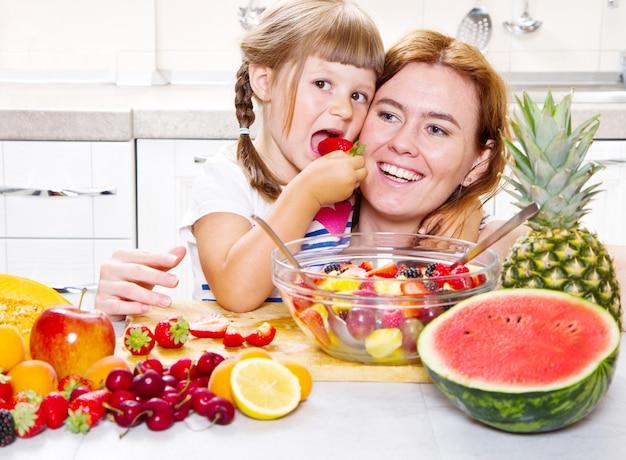 La madre le da a la niña una ensalada de frutas en la cocina.