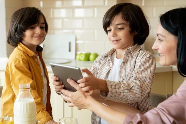 Madre dando a sus gemelos una tableta