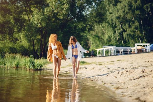 Madre deportiva con linda hija caminando cerca del lago