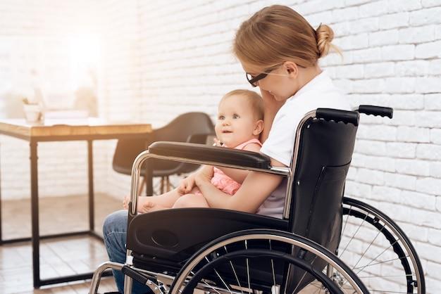 Madre discapacitada en silla de ruedas con bebé recién nacido.