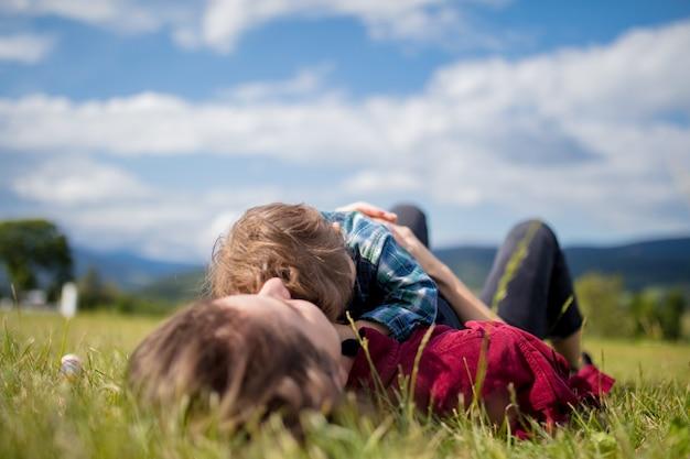 Madre diviértete con un hijo en un prado en las montañas