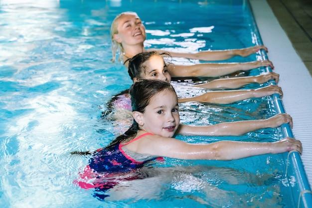 Madre con dos hijas divirtiéndose en la piscina cubierta