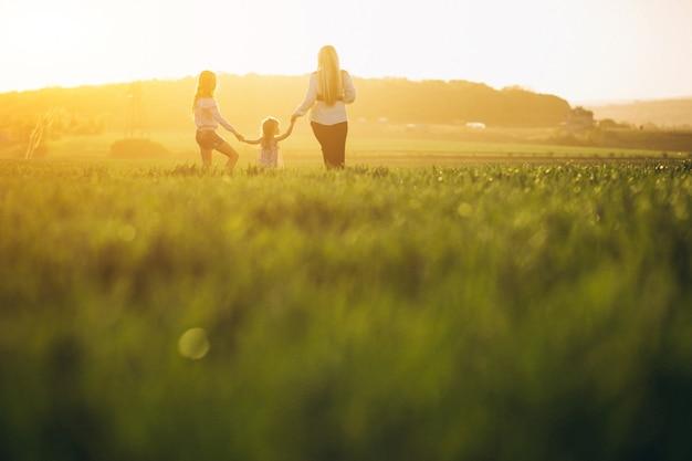 Madre con dos hijas en puesta de sol