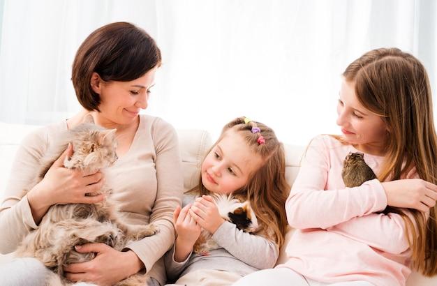 Madre y dos hijas con sus mascotas favoritas en las manos.