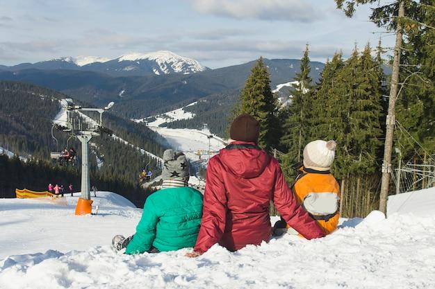 Madre y dos hijos están sentados en una estación de esquí