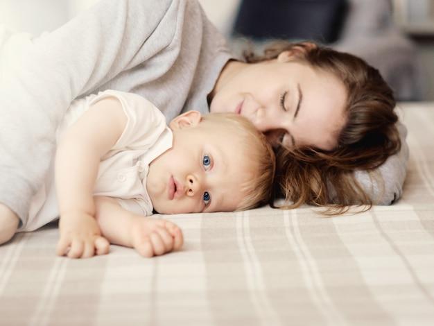 Madre duerme con el niño en la cama