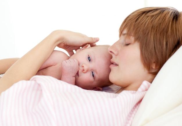 Madre durmiendo con su bebé recién nacido
