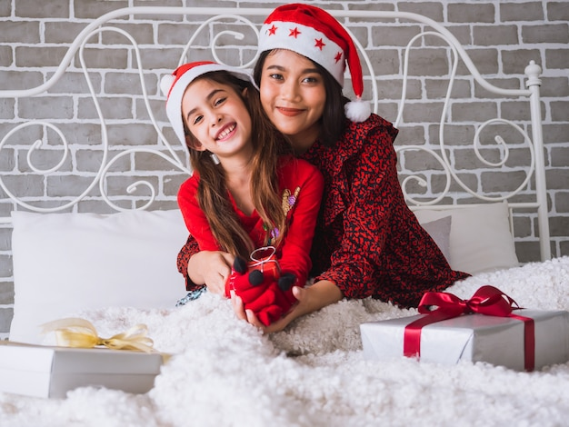 Madre e hija se abrazan felices y celebran la navidad en la cama