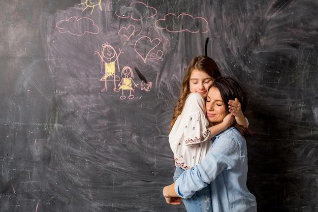 Madre e hija abrazando cerca de pizarra con dibujo