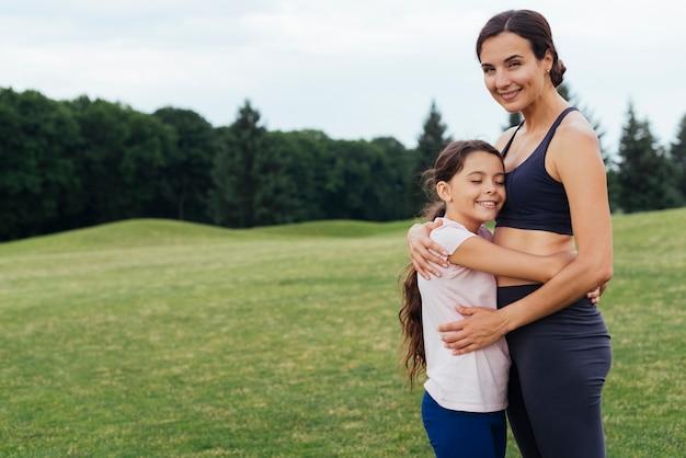 Madre e hija abrazando en la naturaleza
