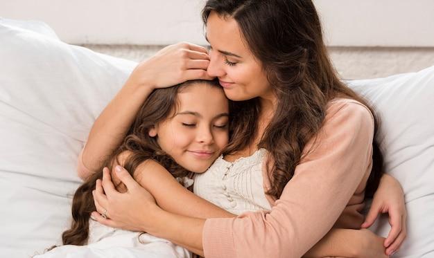 Madre e hija abrazándose en la cama