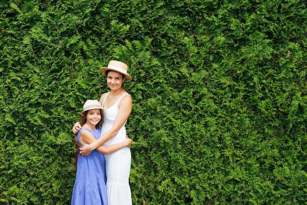 Madre e hija abrazándose frente a arbustos