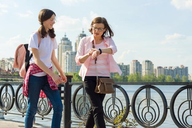 Madre e hija adolescente caminan por la calle