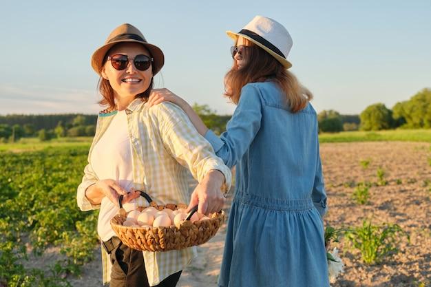 Madre e hija adolescente con una canasta de huevos frescos