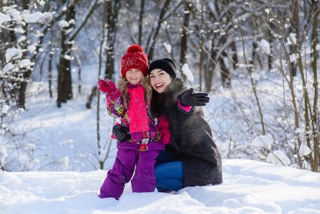 Madre e hija agitando sus manos en el bosque de invierno