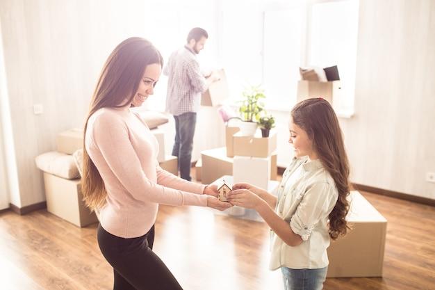 Madre e hija alegres están de pie en la habitación luminosa y sostienen una pequeña casa de juguete que está hecha de madera
