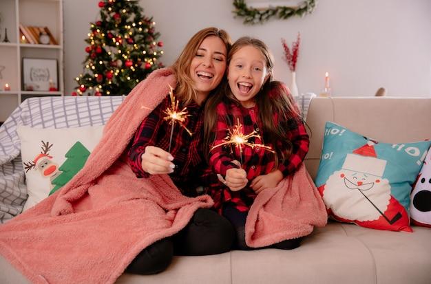 Madre e hija alegres sostienen bengalas cubiertas con una manta sentada en el sofá y disfrutando de la navidad en casa