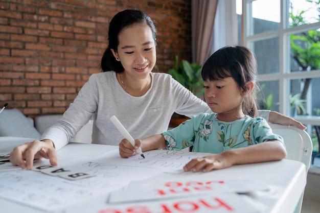 Madre e hija aprendiendo a leer y escribir cartas en casa