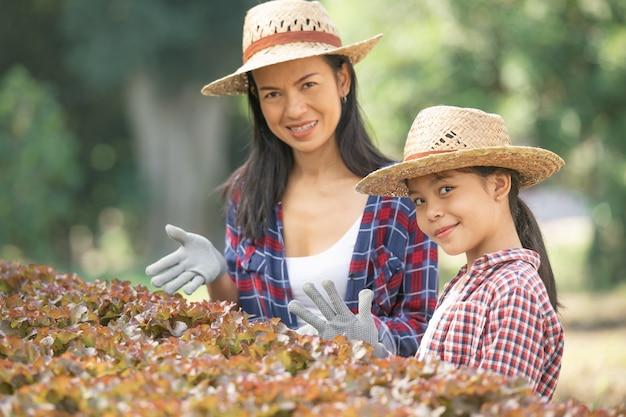 Madre e hija asiáticas están ayudando juntas a recolectar la verdura hidropónica fresca en la granja, el concepto de jardinería y la educación infantil de la agricultura doméstica en el estilo de vida familiar.
