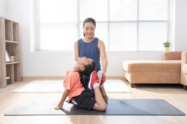 Madre e hija asiáticas haciendo ejercicio en casa están haciendo yoga