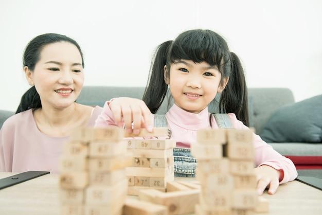 Madre e hija asiáticas jugando juego de apilamiento de torre de bloques de madera en una acogedora casa moderna