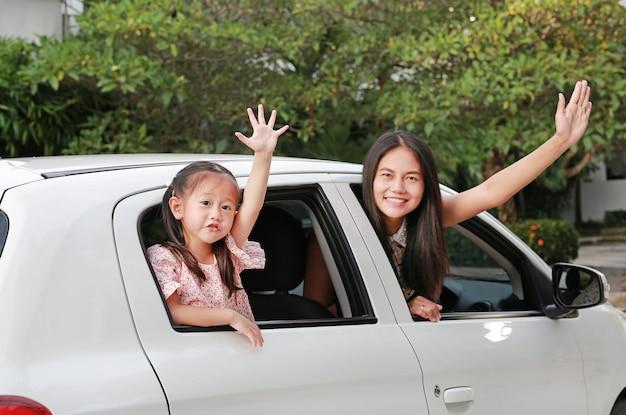 Madre e hija en un automóvil y agitando adiós
