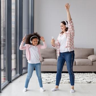 Madre e hija bailando música en casa