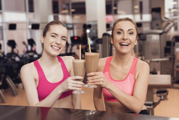 Madre e hija bebiendo batidos de proteína en el gimnasio