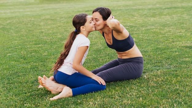 Madre e hija besándose y haciendo ejercicio en la naturaleza.