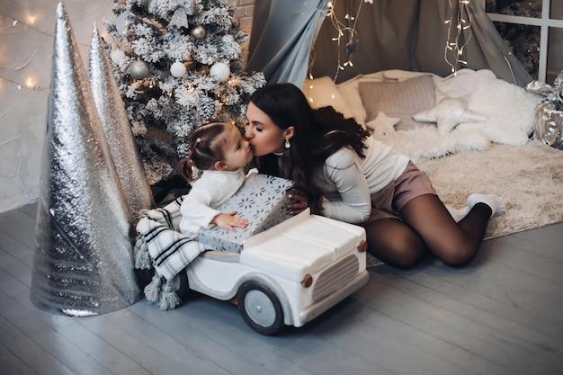 Madre e hija besándose en navidad bajo la nieve.