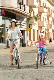Madre e hija en bicicleta por la calle en la ciudad.