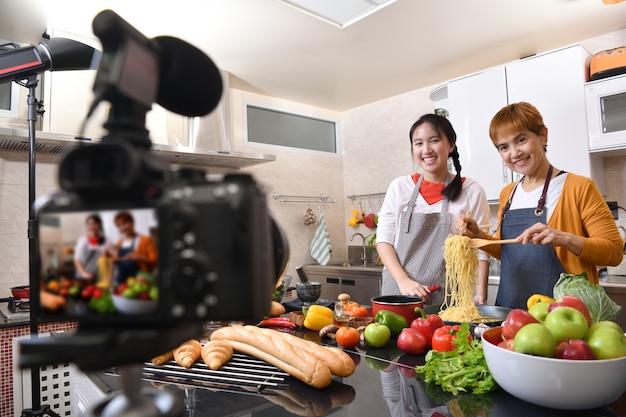 Madre e hija blogger vlogger e influenciador en línea grabando contenido de video sobre alimentos saludables