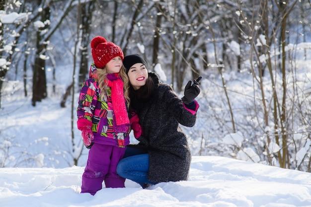 Madre e hija en bosque de invierno