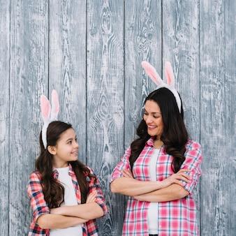 Madre e hija con los brazos cruzados mirando el uno al otro contra el fondo gris de madera