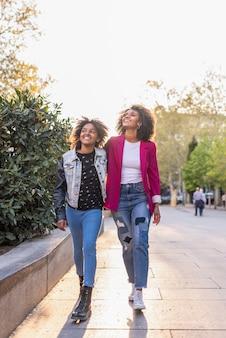 Madre e hija caminando juntos al aire libre.