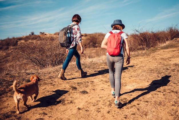 Madre e hija caminando por sendero de montaña
