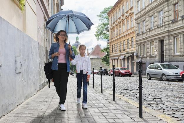 Madre e hija caminando bajo una sombrilla por la calle